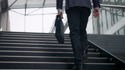 Businessman climbing up the stairs in the building. Confident man dressed in suit on a his successful career path. Low angle shot.