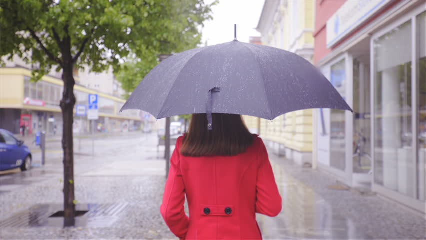 Person in red walk under rain with umbrella 4K. Tracking female person wearing red coat with black umbrella in focus with gimbal stabilizer. Walking through city, surroundings out of focus.