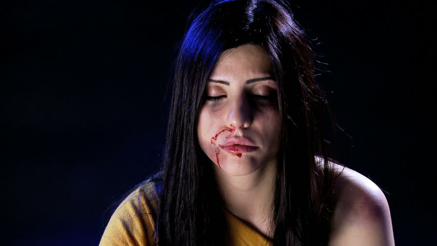 Beautiful woman cleaning blood from face after abuse and domestic violence