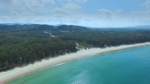 A drone with a camera flies along the coastline to a small island. Transparent water in the ocean, white sand on the beach.