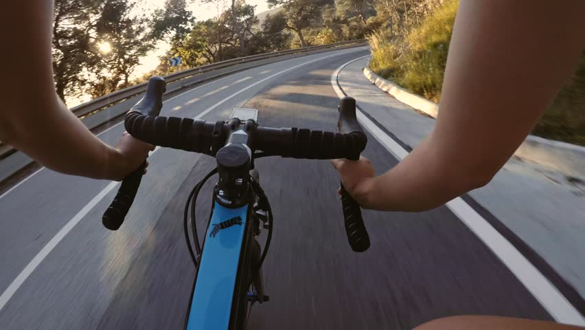 POV shot of female bicycle rider descending mountain road on high fast speed on professional bike in sunset rays falling down and creating beautiful shadows. May '17 in Spain