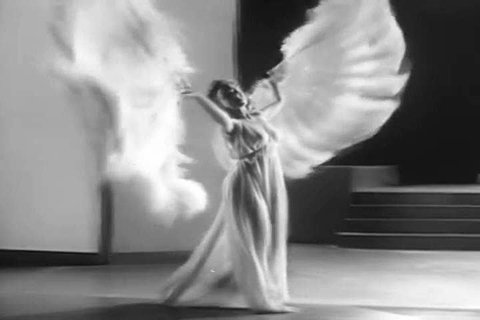 1940s: A dancer performs a beautiful silhouetted dance with gossamer fanned wings on in this 1940s soundie.