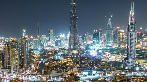 Dubai Downtown night timelapse with Burj Khalifa and other towers paniramic view from the top in Dubai, United Arab Emirates. Traffic on circle road and music fountain show. Zoom out