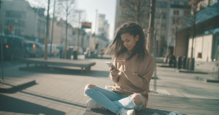 Portrait of young African American woman using phone, outdoors. Beautiful young woman typing on phone during sunny day. | Shutterstock HD Video #27170263