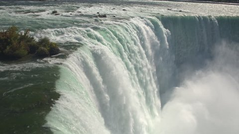 AERIAL CLOSE UP Flying above scenic Niagara Falls along the edge of a cliff. Whitewater rapids breaking and crushing into the bottom of the waterfall. Thick fresh mist rising above the Horseshoe Falls
