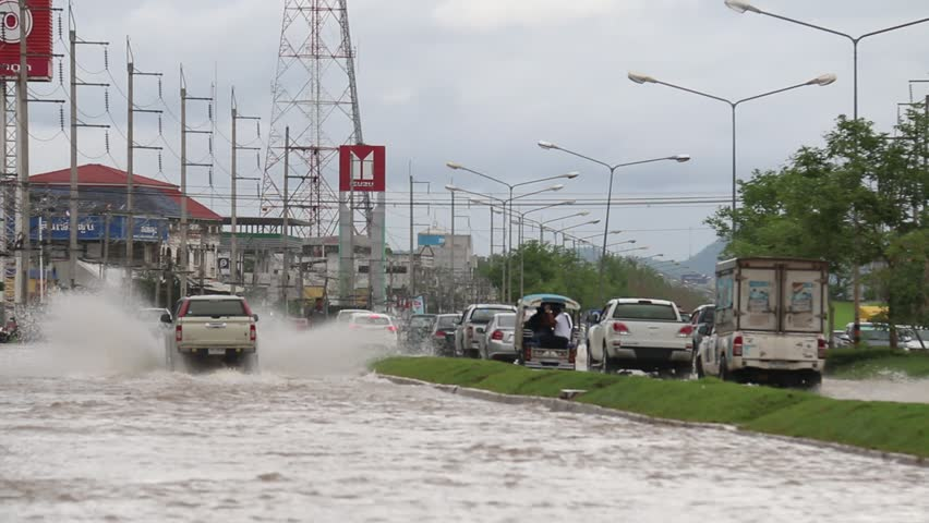 LOEI, THAILAND - MAY 18 2017: Car traffic on a flooded city road, Thailand Storm Flooding Bloor flooded from the heavy rain at LOEI Province, THAILAND on MAY 18 2017.