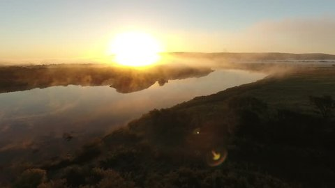 Low flight river valley bent early morning fog clouds Primorye, Vladivostok. Yellow orange sunrise horizon. Wide open space Aerial drone beautiful Russian nature landscape. Romantic cinematic mood.