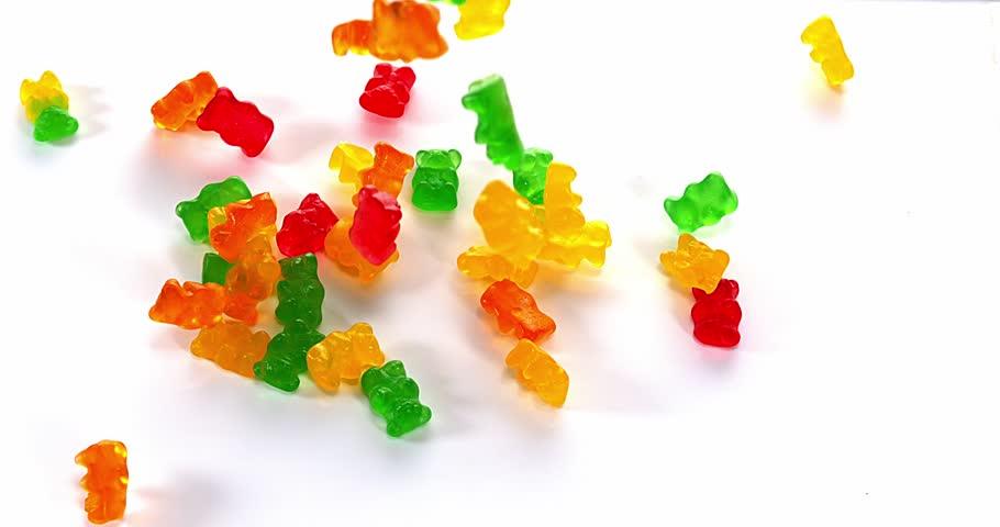 Gold Bears or Gummy Bears falling against White Background, Slow Motion