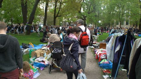 HELSINKI, FINLAND - MAY 27, 2017: A lot of people at the flea market in the city Park. The traditional day of the sale of unnecessary things, called in Finland Cleaning Day. Subjective camera