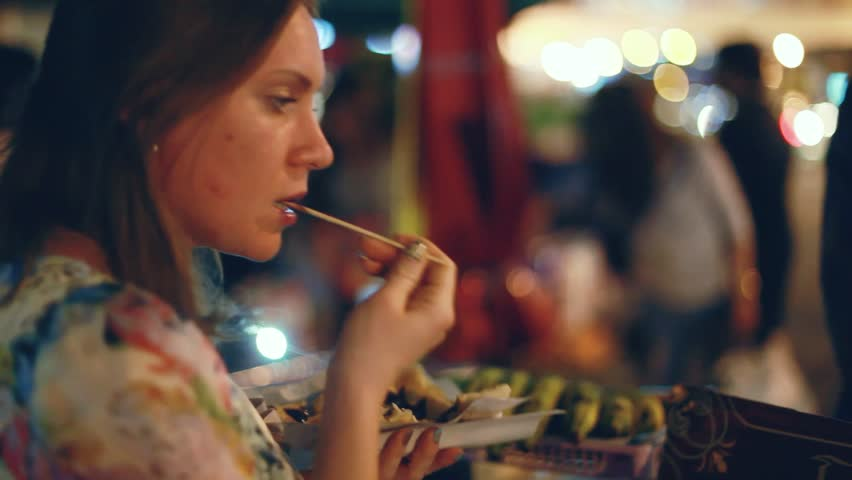 Food For Sale on the Street Food in night market. Woman eats pancake with banana. 1920x1080