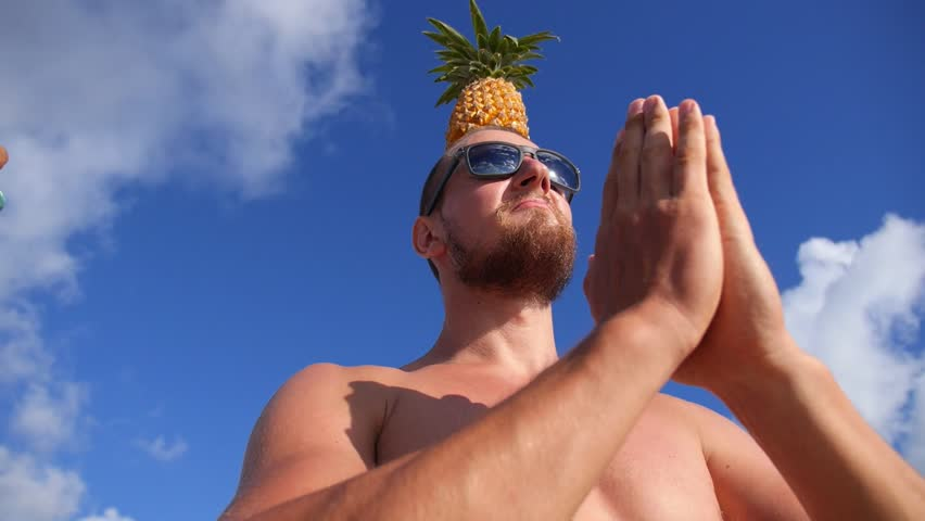 Young Man With Pineapple On Head On Beach Greeting The Sun. Slow Motion. Closeup. HD, 1920x1080.