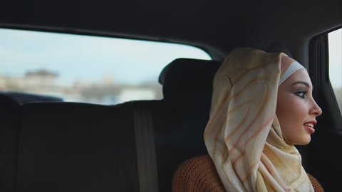 Young happy Middle Eastern woman traveling by taxi. She looking at the city through the window and enjoying the ride