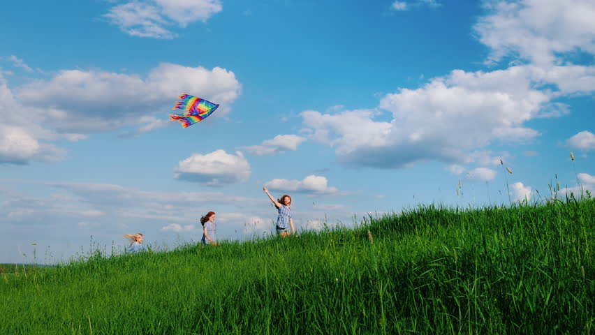 Carefree children play with a kite. Running along the green hill against the blue sky with white clouds. Happy childhood
