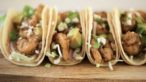 Close up of fresh chipotle shrimp tacos with cotija cheese on a white corn tortillas.