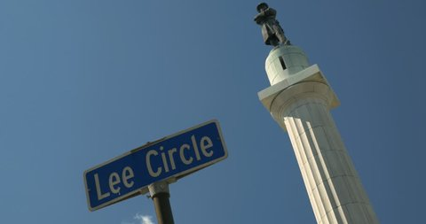 Dutch angle Lee circle Street sign with General Robert E Lee Confederate statue in background with blue sky. The statue was removed by the city on May 19th 2017 4K