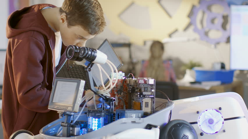 Boy Works on a Fully Functional Programable Robot with Bright LED Lights for His School Robotics Club Project. Shot on RED EPIC-W 8K Helium Cinema Camera.