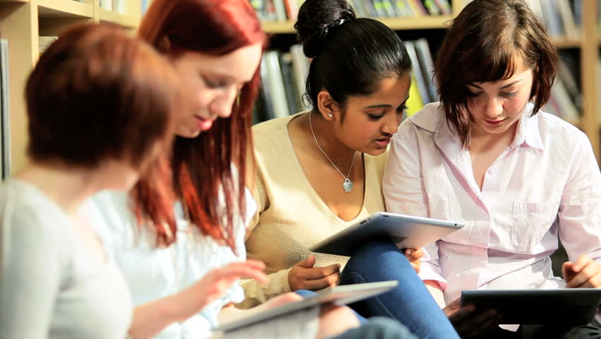 Group of diverse female students using online university internet on tablet computer in information library