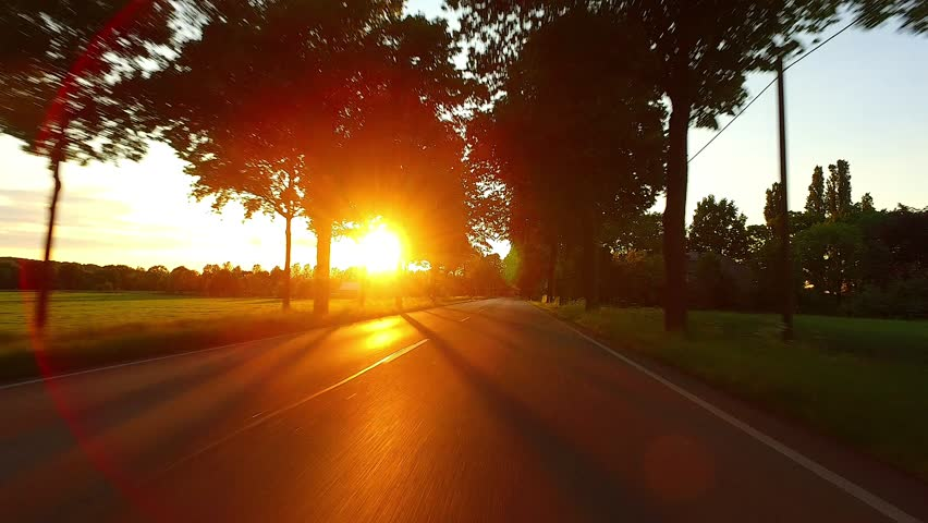 Driving a Car POV on a Scenic Road into Sunset