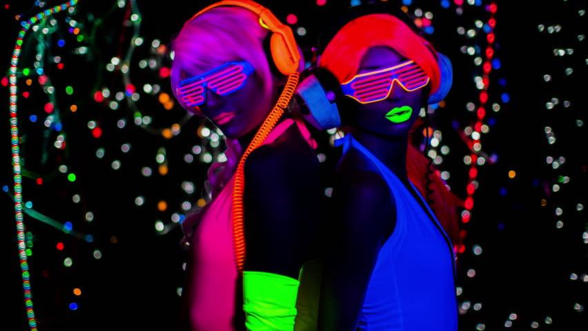 4k fantastic video of 2 sexy cyber glow raver women filmed in fluorescent clothing under UV black light | Shutterstock HD Video #27345289