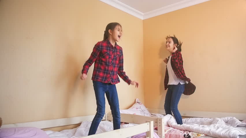 Slow motion video of two cheerful girls dancing and jumping on bed