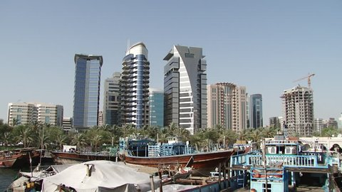 DUBAI, UAE - CIRCA 2008: Tilt-down on the Dhow Wharfage area on the banks of Dubai Creek north of Maktoum Bridge. Hundreds of traditional dhows are docked waiting to load and unload diverse cargo.