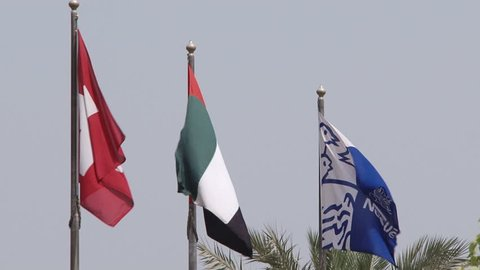 JEBEL ALI, DUBAI, UAE - CIRCA 2008: View of Swiss, Emirates and Nestl_ flags blowing in the breeze. Nestl_'s Middle East headquarters are located in Dubai World Central building Jebel Ali.