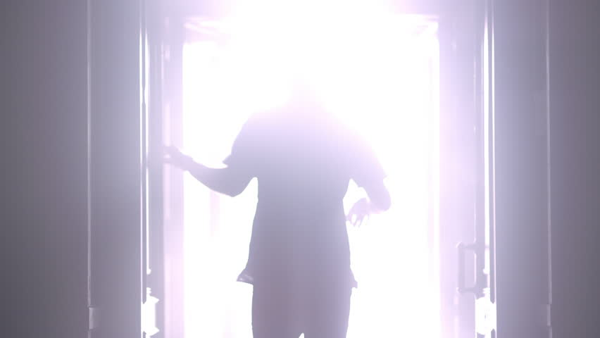 Man silhouette back going to the light at night. Male silhouette going to bright light. Man silhouette walking to light in the darkness. Man open door light in dark. Escape concept