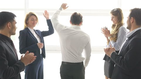 group of businessman's celebrating a success. the man give a high five to a colleague. slow motion