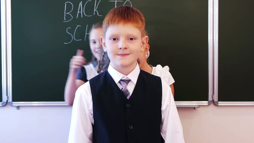 Group of successful schoolchildren giving thumb ups together in the classroom. Back to school is written on chalkboard.  | Shutterstock HD Video #2738240