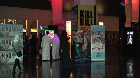 KUWAIT - CIRCA 2013: Medium shot of a cinema foyer decorated with Arabic and Wesern movie posters, in the 'Avenues Mall'. Cinema goers stroll through the foyer waiting for films to start.