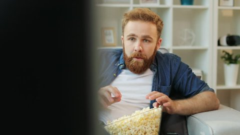 Emotional man with beard watching stressful football match, eating popcorn while sitting in the living room.