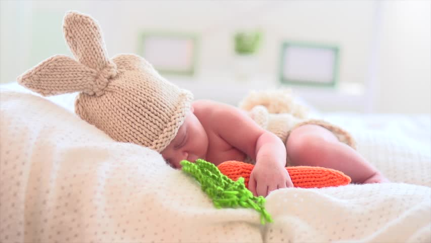 Newborn baby in funny bunny costume. Two weeks old new born baby boy wearing knitted bunny hat with rabbit ears, tail and carrot toy. Adorable infant baby sleeping in his bed. 4K UHD video slow motion