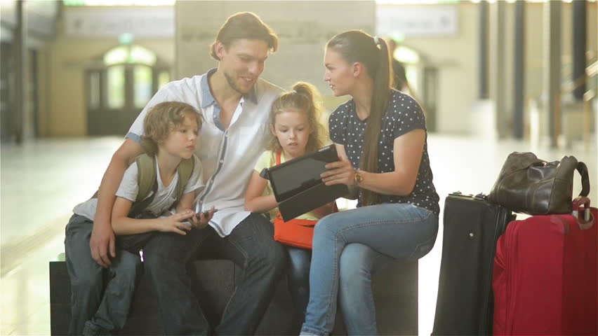 Mother and Father with Two Children are Sitting in the Waiting Room of the Railway Station or an Airport. Pretty Mom is Showing Her Tablet. Kids are Holding Smartphones in Their Hands. | Shutterstock HD Video #27442579