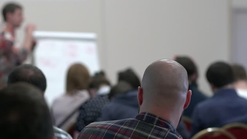 Lecturer speaking to his class in the lecture hall at the university. Skinhead