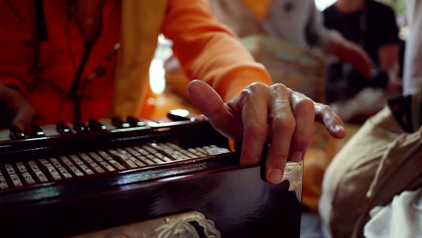 The performance of the kirtan of the hare Krishna in the Krishna temple on the ancient classical instruments. Big game plan the harmonium.