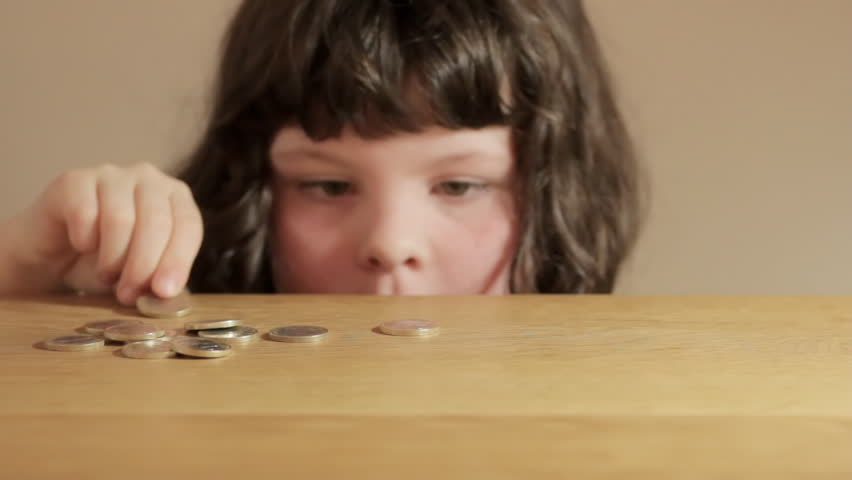 Small girl counting Euro coins