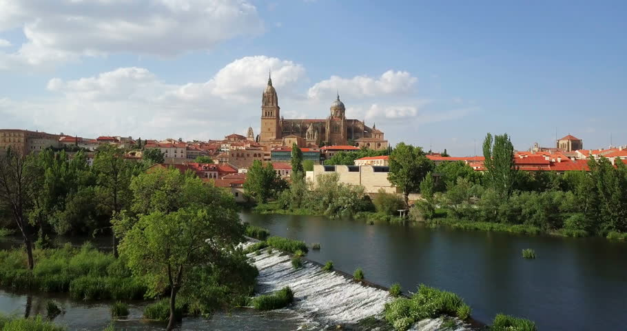 Aerial footage. The Cathedral of Salamanca reflected in the Tormes river. Spain.