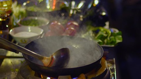 Chef cooks in fired up wok in Shanghai slow motion. Slowmo flames of hot oil with vegetables outside on the road at night in downtown Shouning rd food street in China.