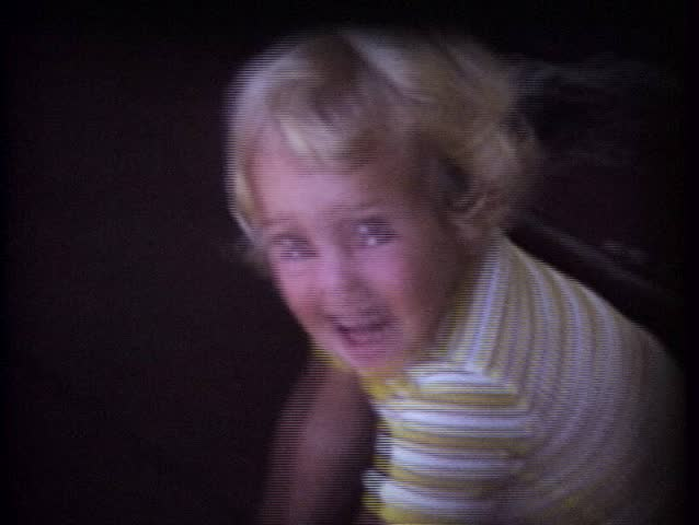 Vintage 8mm Film, A little girl looking at camera and talking to her Dad.  This was shot in the mid-1970s.