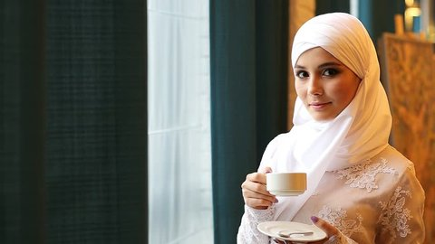 Muslim woman in a white wedding dress with a cup of tea in her hands
