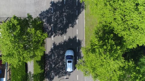 Aerial following car top-down view this grey colored station wagon also called an estate car or estate wagon has sunroof and is driving over two way street with green trees on both sides of street