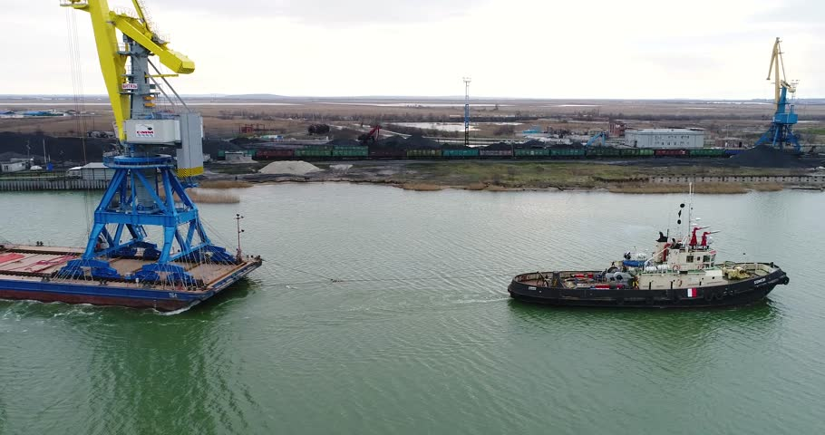 Towing cranes for containers. Large container ship pulled by tugboats. Top down aerial view. Container Cargo freight ship with working crane bridge in shipyard at dusk for Logistic Import Export   Shutterstock HD Video #27530557
