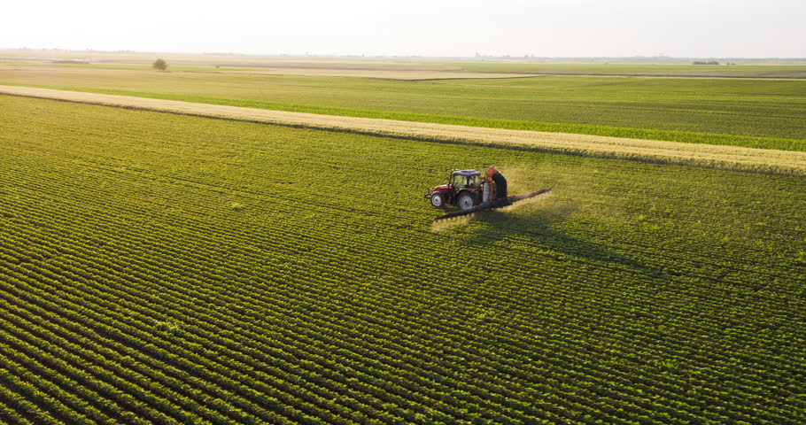 Aerial drone shot of a farmer spraying soybean fields