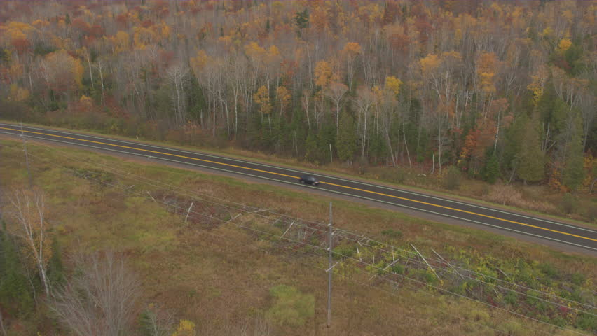 AERIAL: Flying above stunning fall foliage forest and empty interstate highway running through the picturesque countryside. People in black van driving along the expressway enjoying autumn road trip
