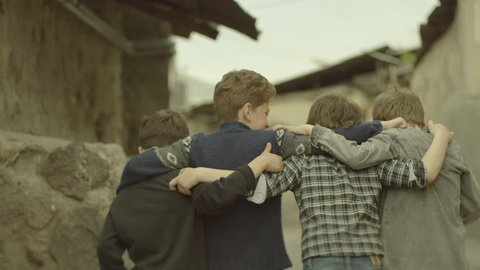 Childhood Memories.  Back view of a group of teen friends enjoying a walk, hugging each other. Vintage times. Shot on RED EPIC DRAGON Cinema Camera in slow motion.