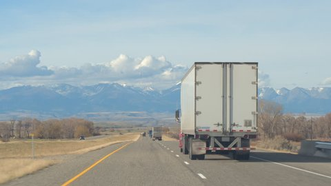 FPV Freight semi trucks transporting goods, personal cars on a road trip, people in SUVs traveling along the busy traffic highway running through farmland countryside towards the Rocky Mountains Range
