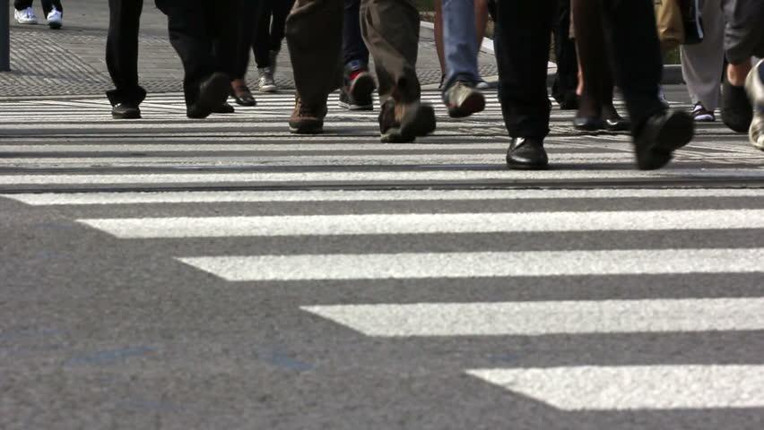 People step across a road by crosswalk or zebra crossing / Pedestrian crossing in a city