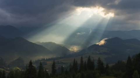 Timelapse of sun rays emerging though the dark storm clouds in the mountains with pine tree forest on a foreground