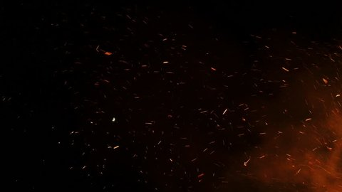 Flying glowing bonfire embers into night sky