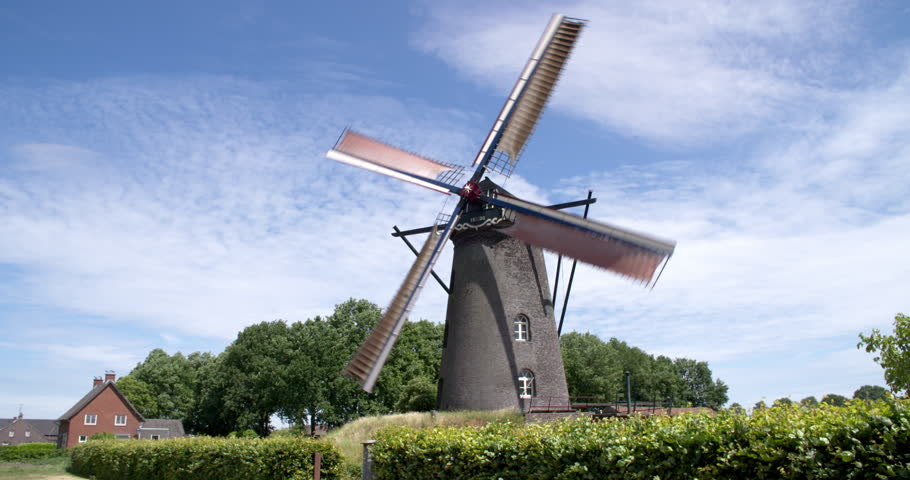 ROGGEL, NETHERLANDS - JUNE 11, 2017: Working windmill in the province Noord-Limburg, blue sky with clouds, long shot, 4K